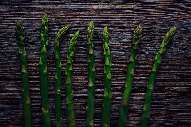 Asparagus raw vegetables in a row on aged wood background photo