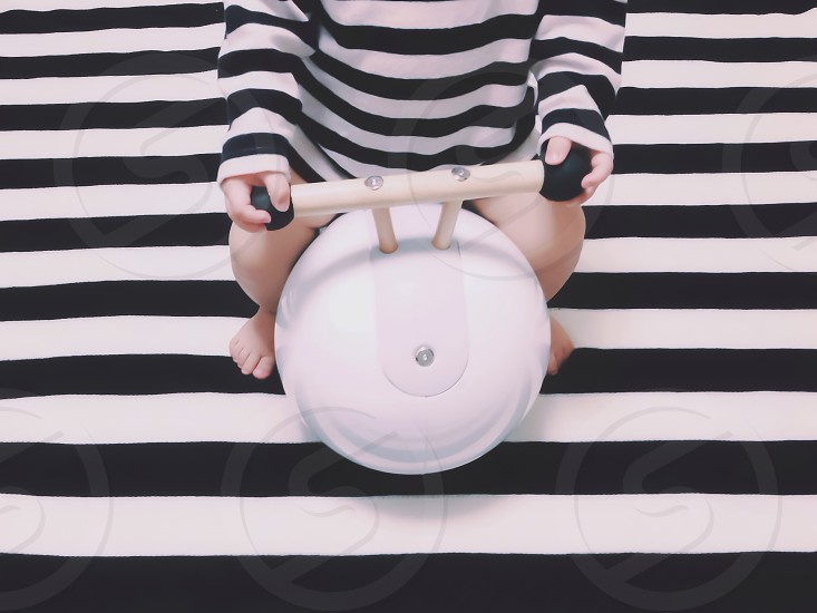 toddler in black white striped long sleeved shirt sitting photo