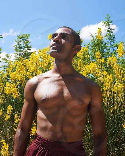 Skin deep fit strong man standing in the sunlight spotlight nature photo
