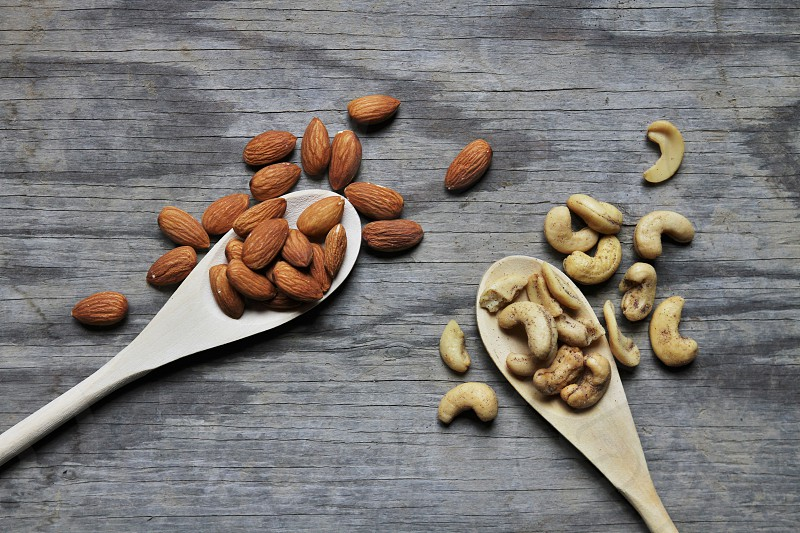 almonds cashews on a table top wooden spoons top view photo