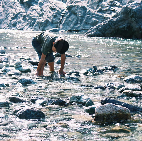 boy in gray shirt playing in body of water with rocks during daytime photo