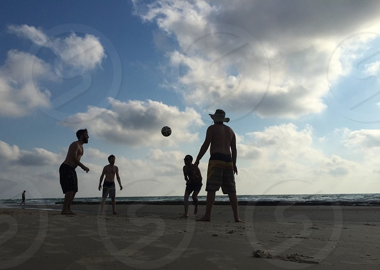 four men playing with a ball on a beach under a cloudy blue sky photo