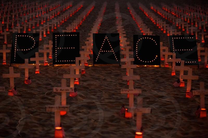 peace neon lights on white grave cross photo