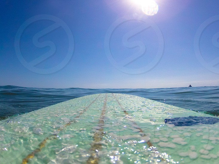 surfing green aqua surfboard sunny clear cloudless blue sky wax surf water ocean pov wide angle photo