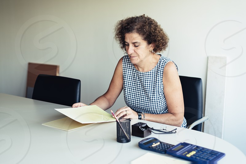 Businesswoman with folders on desk in office photo