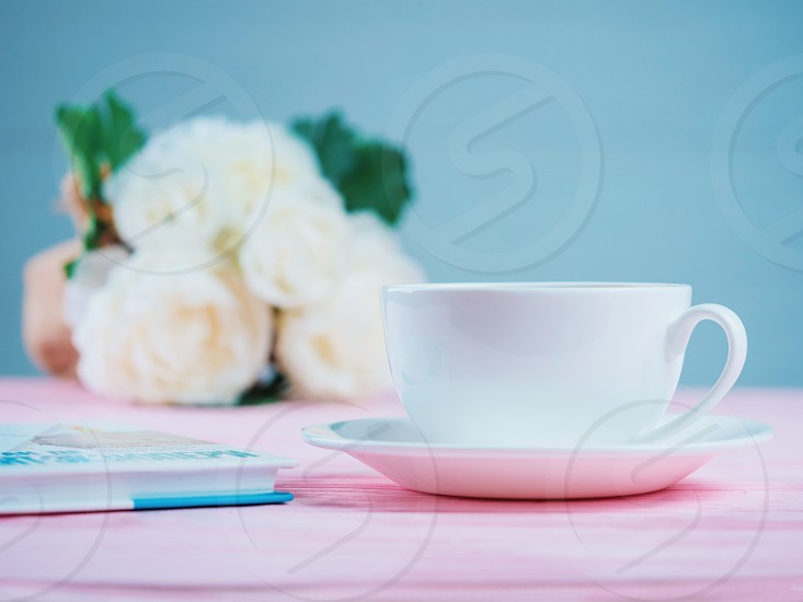 Romantic background with cup of tea or coffee rose flowers and book over light pink wooden table photo