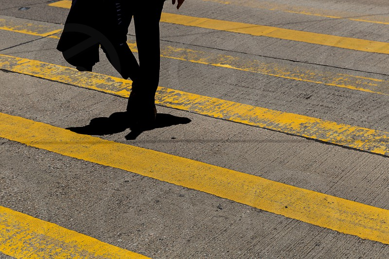 Businessman wearing suit and jacket crossing road in Hong Kong photo