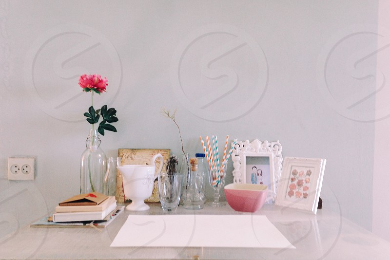 white paper sheet on table with picture frames and books photo