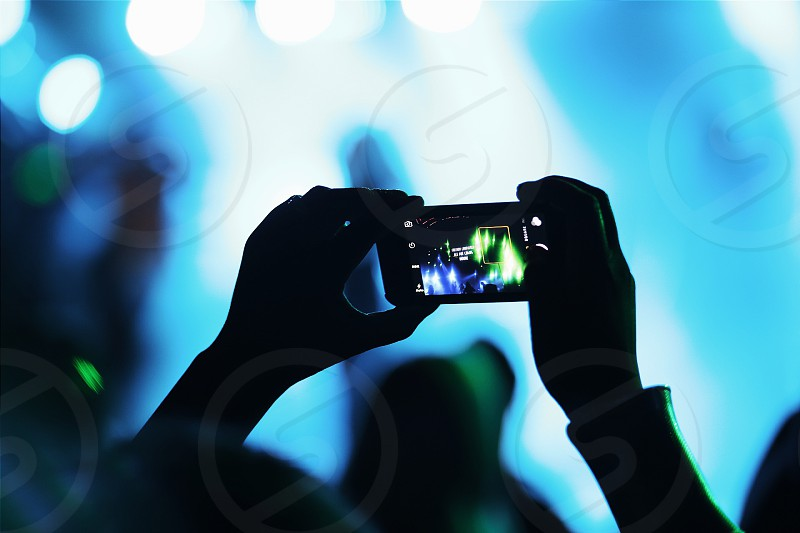 person capturing image of green blue lights using smartphone photo