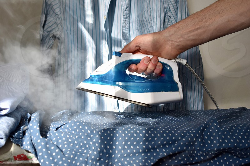 Man ironing a pile of shirts. photo