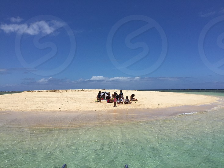 group of people staying on white beach shore during daytime photo