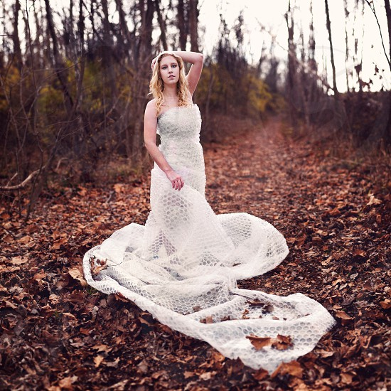 woman in white wedding gown standing on dried leaves photo