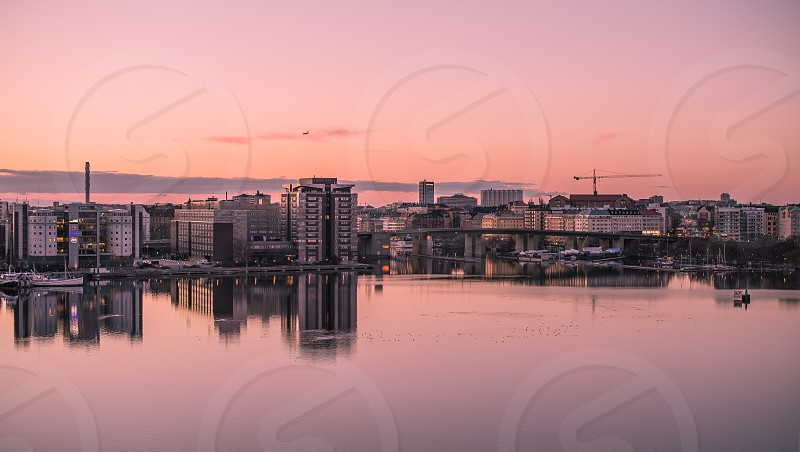 photograph city by water with pink sky photo