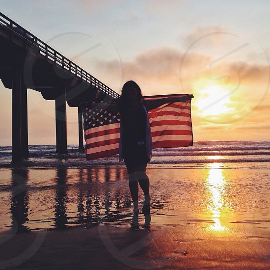 woman holding the american flag on a sunset photo