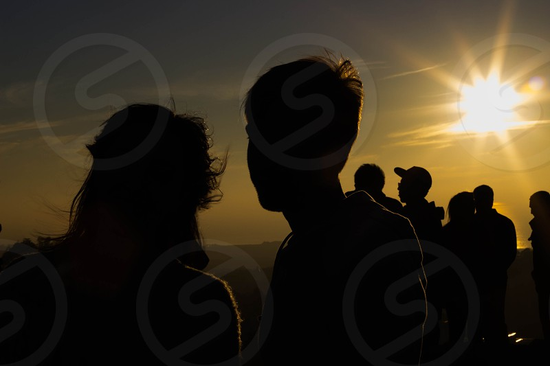 Silhouette people sunset twin peaks sun in the back.   photo