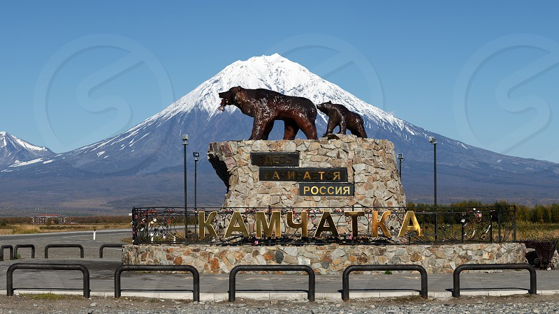 "KAMCHATKA PENINSULA RUSSIA - SEP 24 2017: Panoramic view of sculpture of Kamchatka brown bear family ""She-bear with teddy bear"" inscription: ""Here begins Russia. Kamchatka"" on background of volcano photo"