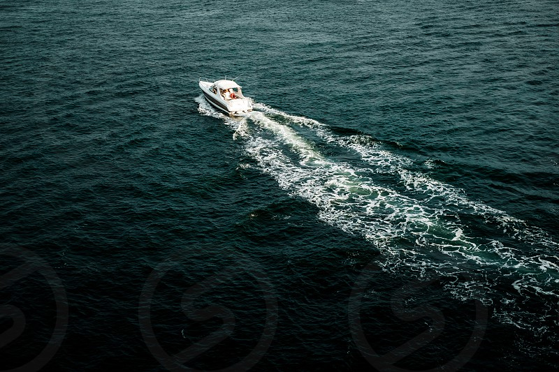 aerial photo of white powerboat on beach during daytime photo
