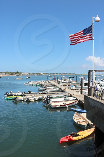 View of a wooden pier with boats docked around it and an American Flag photo