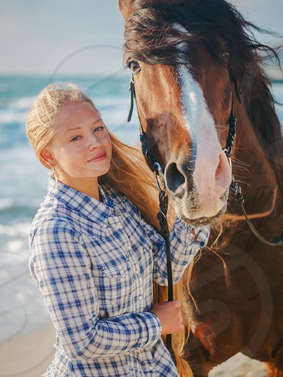Beautiful fair-haired girl in armor with a horse on the background of the sea. blonde woman near black horse at sea beach. Beautiful woman wearing casual clothing enjoying sunrise morning photo