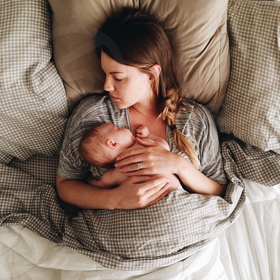 woman in grey shirt on bed cuddling baby on bosom photo