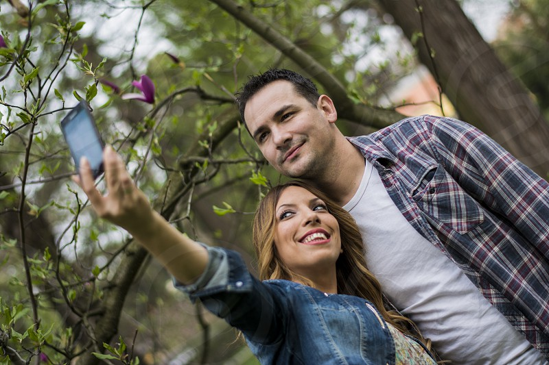 Beautiful young couple taking selfie in the park. photo
