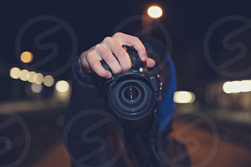 Young man photographing on the street in the night. photo