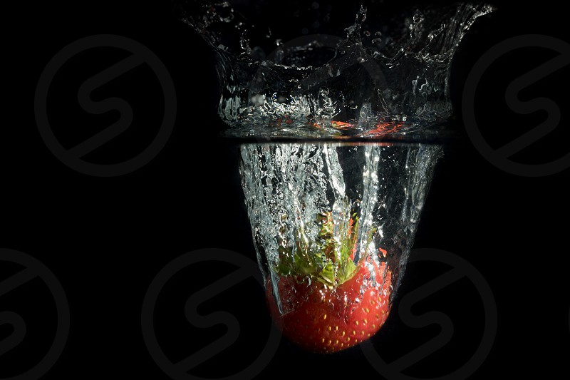 Strawberry falls deeply under water with a splash. All is on the black background.  photo