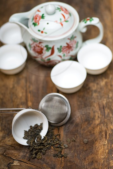 dry green chinese tea setwith strainer closeupcups and teapot on background over old wood board photo