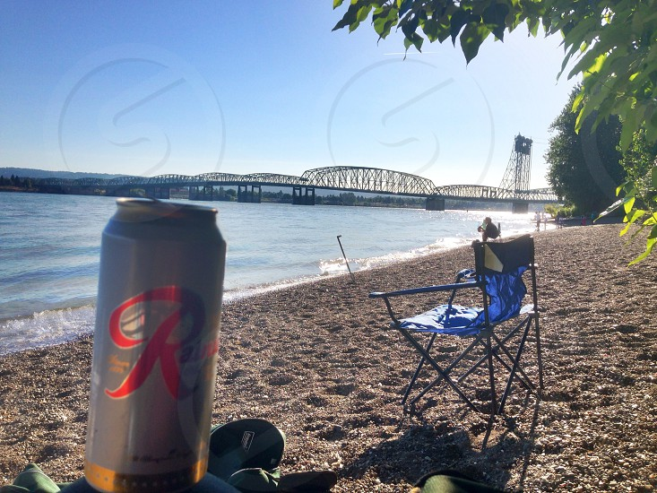 white and red labeled beverage can on ground near blue camping chair on beach shoreline overlooking bridge under blue sky during daytime photo