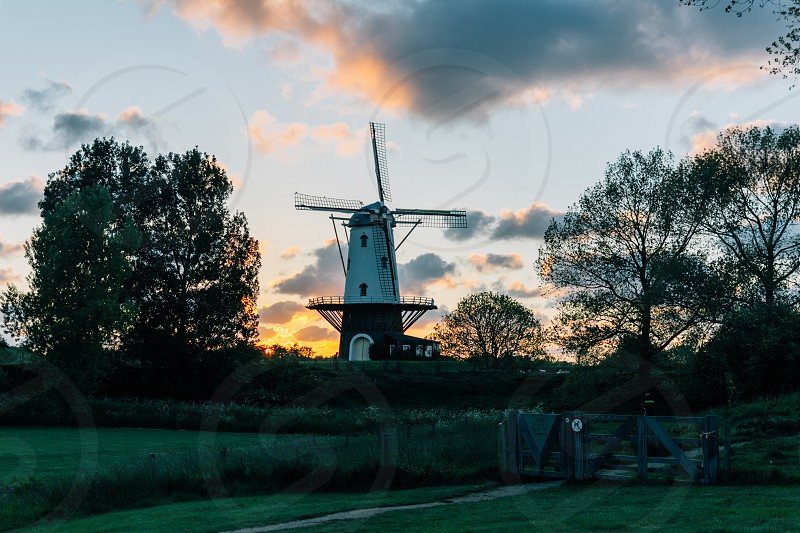 white and brown windmill near green leaved trees on pasture under orange sunset photo
