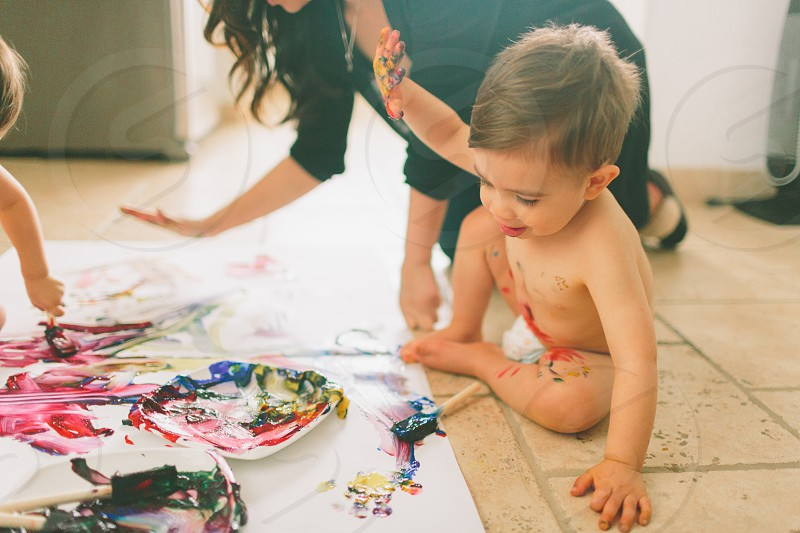 A little boy getting messy and painting at home.  photo
