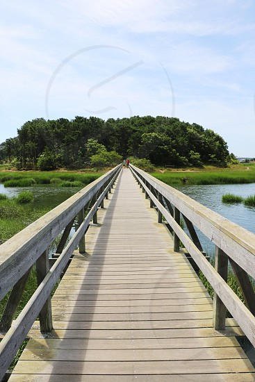 Looking down a long wooden bridge that goes across a small river two people are walking photo