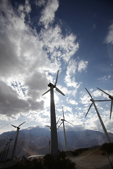 A series of tall windmills silhouetted against a mountain range blue skies and white clouds. photo