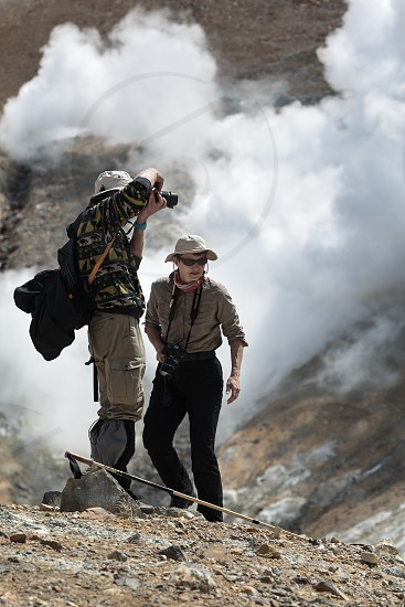MUTNOVSKY VOLCANO KAMCHATKA PENINSULA RUSSIA - JULY 4 2014: Hiking in Kamchatka - tourists (man and woman) photographing and looking the steaming (smoking) fumarole on crater active Mutnovsky Volcano on sunny day. photo