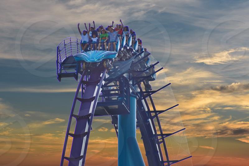 Orlando Florida. September 2 2018.  Nice People enjoying Kraken rollercoaster at Seaworld on colorful sunset backround. photo