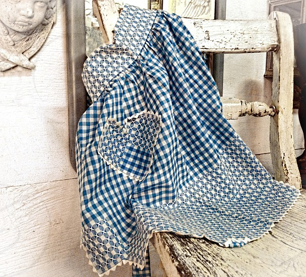 Vintage blue and white checked apron hangs over a white chair with peeling paint. photo