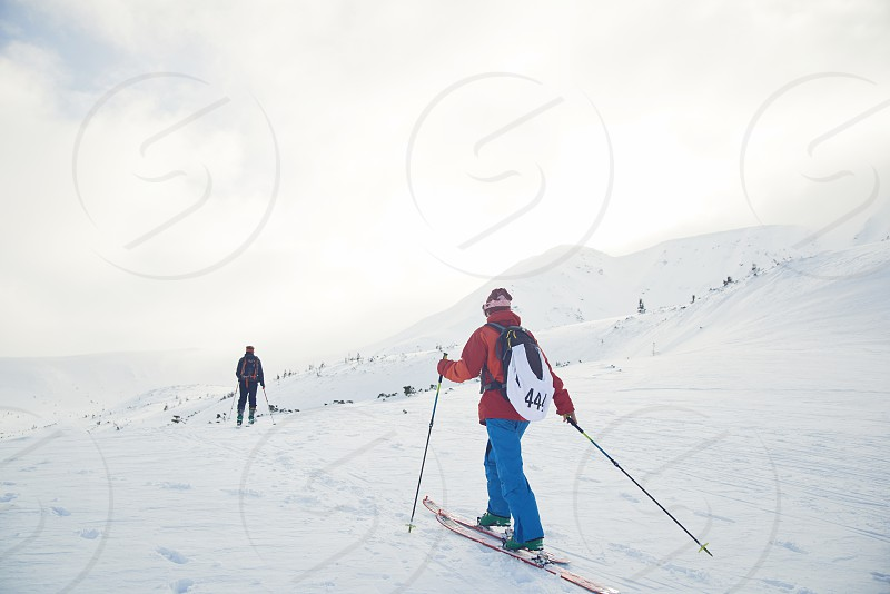 Ski touring couple hiking up a summit in mountains photo
