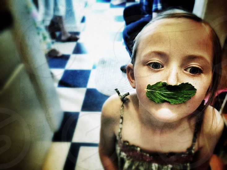 girl with a leaf over her mouth photo