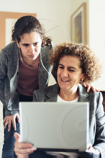 Mother wirh laptop teaching daughter personal finance management photo