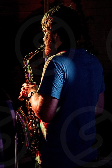 man in blue shirt playing a wind musical instrument photo