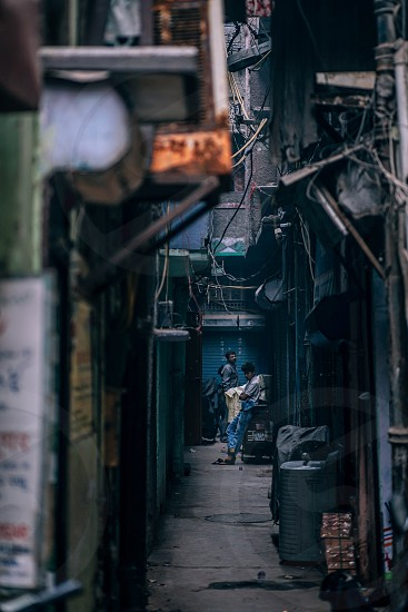 Narrow Indian street with 2 guys at the end. photo