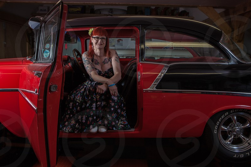 Tattooed lady sitting in vintage Chevrolet car. photo