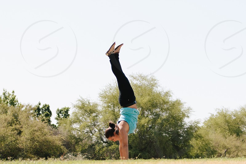 person doing a hand stand on a grass field photo