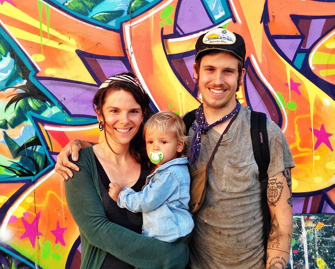 couple standing by the graffiti with their child photo