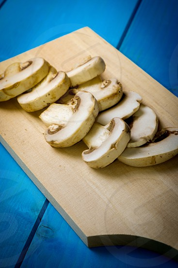 Freshly cut champignons mushrooms placed on a wooden chopping board photo