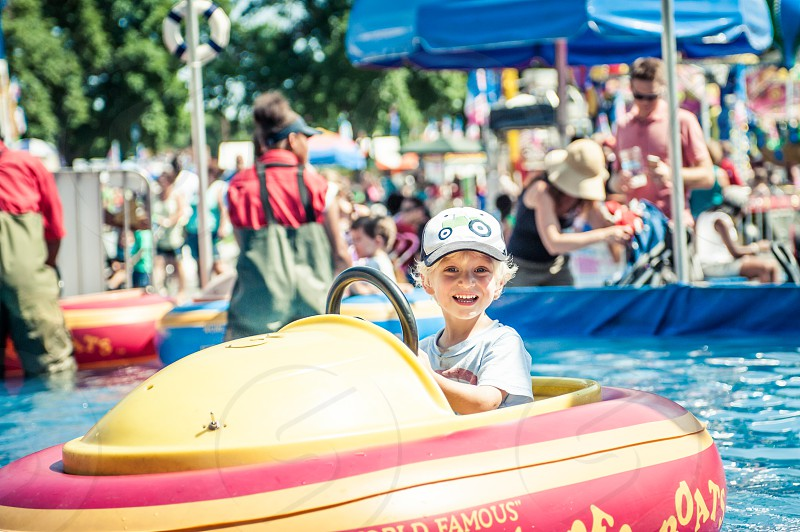 boy child youth happy fun excitement excited thrilled smile teeth bumper boats festival carnival amusement park park play ride rides driving boat red yellow blue pool water summer photo