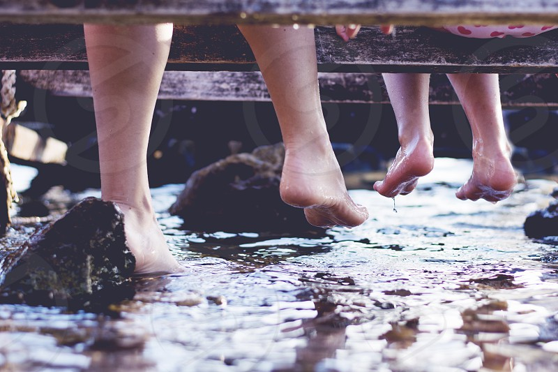 Mother and daughter sitting on a pier with legs down in water barefoot enjoying summer. photo