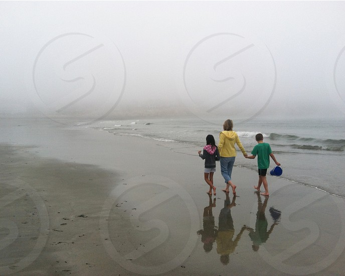 woman and two kids near the surf on foggy beach photo