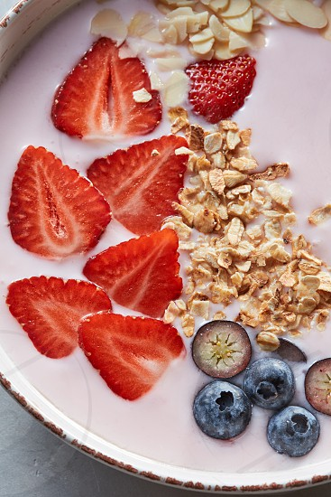Dietary homemade natural breakfast with fresh organic ingredients - berries granola nuts and milk in a ceramic bowl on a gray table. Top view. Concept of healthy dieting food. photo