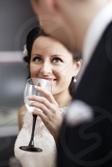 Elegant young woman in a white dress drinking white wine at a function and smiling up at her male partner photo